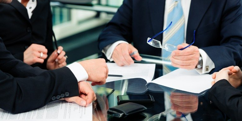 people-in-business-suits-with-paperwork-at-desk